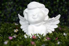 Free White Angel Ceramic Figurine On Green Grass With White And Purple Flower Stock Photos - 82947213