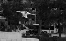 Free Man In White Shirt And Black Pants Playing Skateboard Near Green Tree During Daytime Royalty Free Stock Photo - 82947995