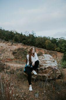 Free Woman In White Long Sleeve Shirt Black Leggings Siting On Brown Rock Royalty Free Stock Image - 82948276