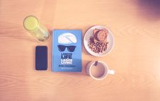 Free Space Gray Iphone Beside Blue Labeled Book Near White Ceramic Cup With Liquid Content Royalty Free Stock Photos - 82948308