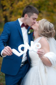 Free Newly Wed Couple Kissed Each Other While Holding Love Cutout Royalty Free Stock Photos - 82949078