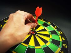 Free Person Holding Red Dart On Green Yellow And Black Dart Board Royalty Free Stock Photo - 82949255
