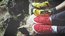 Free Man In Yellow And Black Low Top Sneakers Beside Red And White Low Top Sneakers Royalty Free Stock Photo - 82949695