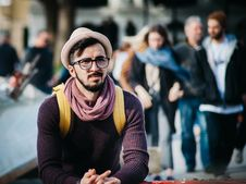 Free Man Sitting Next To Couple Of Person Walking On The Street During Daytime Stock Photos - 82949833