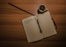 Free Pen On Notebook Beside A Teacup On Brown Wooden Plank Royalty Free Stock Photography - 82950897