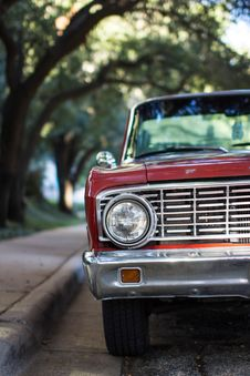Free Front Of Red Classic Ford Pickup Truck Parked On Street Next To Trees Stock Images - 82951884