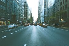 Free Cars Going From And Through On Road In Middle Of High Rise Buildings Royalty Free Stock Images - 82952679