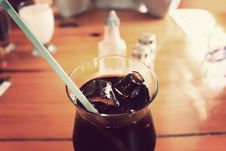 Free Glass Cup With Black Liquid And Green Straw On Brown Wooden Royalty Free Stock Image - 82953256