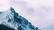Free Paraglider Against Cloudy Mountain Peak Stock Photos - 82954263