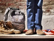 Free Person In Blue Jeans And Brown Suede Shoes Standing Near Camouflage Backpack Brown Hiking Boots And American Flag On Floor Royalty Free Stock Images - 82957169