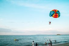 Free People Paragliding On Beach Over Sea Stock Photo - 82959590