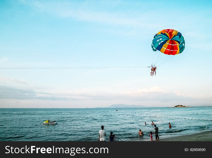 People paragliding on beach over sea