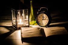Free Candle Lamp Green Bottle Black Alarm Clock And Book Royalty Free Stock Images - 82960869
