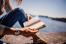 Free Woman Wearing Blue Denim Jeans Holding Book Sitting On Gray Concrete At Daytime Stock Photography - 82961052