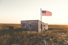 Free U.s Flag On Green Grassland In Front Of Gray Concrete House Stock Images - 82964674