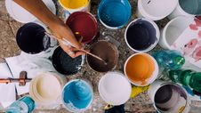 Free Person Holding Paintbrush In Brown Paint Bucket Royalty Free Stock Images - 82965729