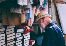 Free Man In Brown Sun Hat Facing Black Covered Piled Books Royalty Free Stock Photos - 82974688