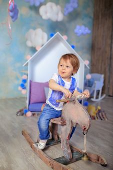 Free Boy In Blue And White Crew Neck T Shirt Riding On Wooden Rocking Moose Stock Image - 82976471