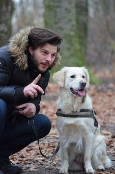 Free Man Wearing Black And Brown Fur Hoodie Jacket And Blue Pants Holding Dog Leash Beside White Short Coat Dog Stock Photo - 82976960