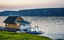 Free White Boat Beside Wooden House On Water Near Forest Royalty Free Stock Photos - 82977118