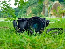 Free Black Sony Dslr Camera On Green Grass In Front Of Brown And Green Mountain Royalty Free Stock Image - 82977976