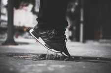 Free Grayscale Photo Of Person Wearing Adidas Nmd Jumping On Puddle Stock Images - 82978084