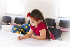 Free Girl In Red Short Sleeve Dress And Flower Headband Holding Pen And Writing On Paper On Table Stock Images - 82979094