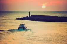 Free Sunset With Lighthouse And Boat Coming Toward Land Royalty Free Stock Photos - 82979828