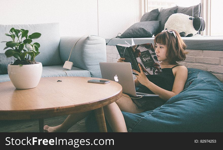 Woman Sitting on Bean Bag White Using Macbook in Front of Round Table With Green Leafed Plant