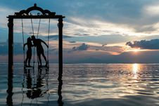 Free Silhouette Of Couple Kissing Standing On Swing In Calm Sea During Sunset Royalty Free Stock Photo - 82981765