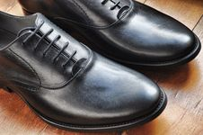 Free Black Leather Shoes On Brown Wooden Tile Floor Royalty Free Stock Image - 82981806