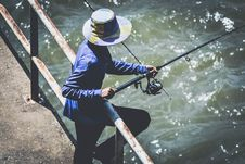 Free Person In Blue Long Sleeve Shirt And Black Pants Using Fishing Rod Stock Image - 82982761