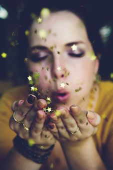 Free Woman In Yellow Shirt Blowing A Gold Star Glitter Royalty Free Stock Photo - 82983585
