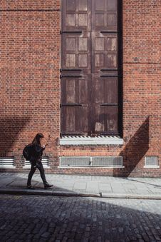 Free Woman In Black Jacket And Black Pants Walking Along The Road Near The Brown Bricked Building Royalty Free Stock Photos - 82984818