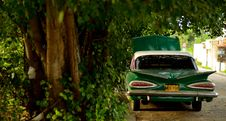 Free Green Vintage Sedan Under Green Trees On A Sunny Day Royalty Free Stock Images - 82985319