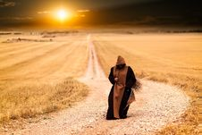 Free Person In Brown And Black Robe In The Middle Of The Road Royalty Free Stock Images - 82986259
