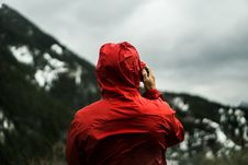 Free Person In Red Hoodie Taking A Photo In Front Of Mountain Stock Images - 82989744