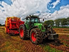Free Green Tractor Pulling Red Bin On Field At Daytime Royalty Free Stock Image - 82990176