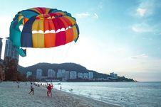 Free Parachutist Lands On Beach Stock Photo - 82990420