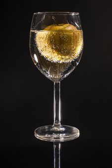 Free Clear Wine Glass Filled With Clear Beverage With Yellow Round Fruit Royalty Free Stock Photography - 82991737