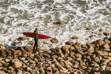Free Man Wearing Wetsuit And Holding Red Surfboard On Shore Stock Photos - 82992763