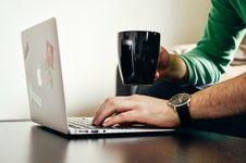 Free Person Wearing Green Long Sleeve Shirt Holding Black Ceramic Mug And Macbook Air Stock Image - 82992961