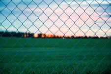 Free Sunset Over Field Through Fence Stock Images - 82992974