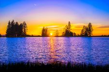 Free Blue And Orange Sunset Over Lake With Tree Silhouettes Stock Images - 82994794