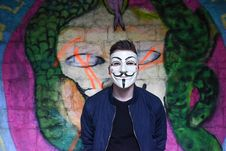 Free Man In White Mask In Black Crew Neck Shirt And Blue Zip Up Jacket Infront Graffiti Wall Royalty Free Stock Photography - 82995277