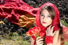 Free Woman Wearing A Red Scarf Holding Red Flowers Royalty Free Stock Photos - 82995998