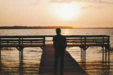 Free Man Walking Out On Dock Of Water At Sunset Royalty Free Stock Photos - 82997618