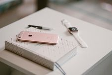 Free Rose Gold Iphone 6 S On Top Of White Covered Book Stock Image - 83008761