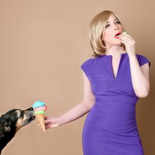 Free Woman In Purple Split Neck Cap Sleeve Bodycon Dress Holding Cone Of Ice Cream Licked By Black Tan Dog Stock Photos - 83009703
