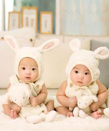 Free 2 Babies Wearing White Headdress White Holding White Plush Toys Royalty Free Stock Photo - 83010135
